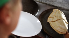 Chef takes pancake from professional griddle to plate Stock Footage