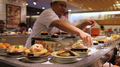 Chef prepares sushi near conveyor belt in a Japanese restaurant in Tokyo, Japan Stock Footage