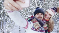 Nice young couple taking photo in snowbound forest Stock Footage