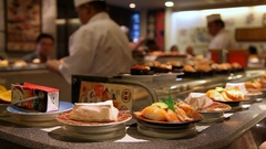 Chef prepares sushi near conveyor belt in a Japanese restaurant in Tokyo, Japan Stock Footage