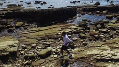 Side view tracking shot of a young man running on a rocky ocean beach shoreline. Stock Footage
