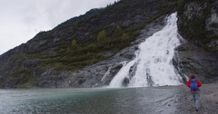 Tourist hiking woman hiker in Alaska walking by glacier and waterfall Stock Footage