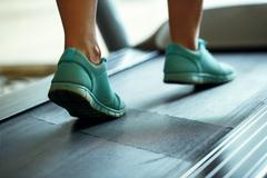 Foot of woman running on treadmill Stock Photos
