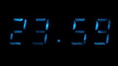 Digital clock shows the time of 23 hours 59 minutes to 00 hours 00 minutes Stock Footage