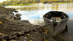 The boat is attached by a chain to the shore Stock Footage