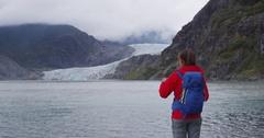 Hiking tourist on Alaska travel taking photo of glacier Stock Footage