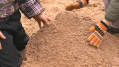 Children playing with sand in outdoor sandbox Stock Footage