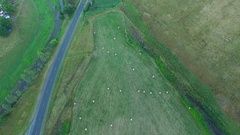 Forward flight high up above hay bales and road looking straight down - Stock Footage