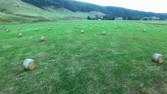 Fast backward flight very low above hay bales in green field Stock Footage
