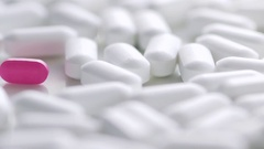 One pink pill amongst a group of white pills Stock Footage