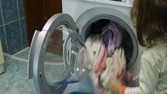 Girl child takes the clean clothes from the washing machine. Stock Footage