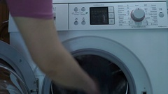 Woman loading the dirty laundry in the washing machine. Stock Footage