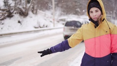 Woman in bright winter clothes hitchhiking in winter at the road Stock Footage