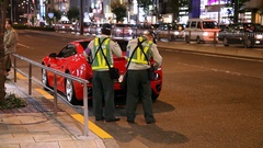 Traffic officers write parking violation ticket for Ferrari car in Tokyo, Japan Stock Footage