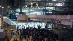 Busy crossing at Osaka station crowd of people at night bright lights  Stock Footage