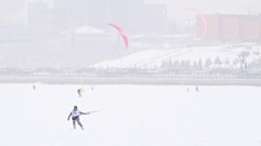 A lot of snow-kite sportsmen's rides on the ice river - winter extremal sport at Stock Footage