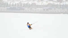 Snow-kite sportsmen in yellow suit rides on the ice river - winter extremal Stock Footage