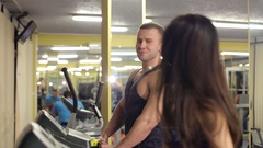 A young couple is engaged on a treadmill in the gym. Stock Footage