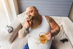 Drunk fat man eating unhealthy food Stock Photos