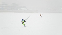 Snow-kite sportsmen in green suit rides on the ice river - winter extremal sport Stock Footage