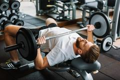 Tight powerful man in gym Stock Photos