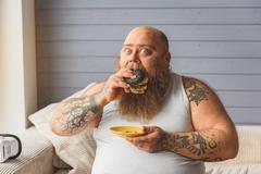 Fat man eating unhealthy burger at home Stock Photos