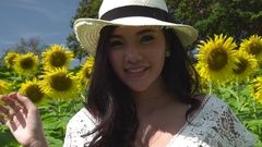Asian woman smiling at the camera in a sunflower field Stock Footage