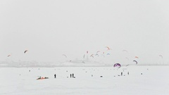Winter extremal sport - a lot of colorful snow-kites over the ice river in front Stock Footage