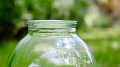 Pouring milk into glass jar outdoor. Close up Stock Footage