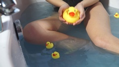 Close-up of a model in the jacuzzi legs among ducklings Stock Footage