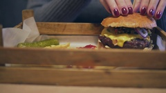 Fried potato chips with big burger lay at the wooden server. Burger is prepared Stock Footage