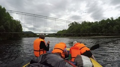 Rafting boat floats under dangerously low hanging suspension bridge over rive Stock Footage