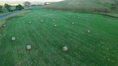 Forward low flight over hay bales in green field in Mitta Mitta Valley Stock Footage