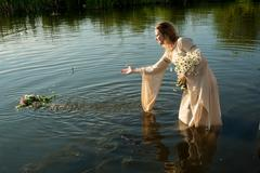 Attractive woman lowers wreath in water Stock Photos