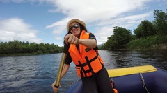Young woman dressed in orange lifejacket actively rowing oar in rafting boat Arkistovideo