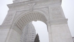 Arch at Washington Square Park tilting to Christmas tree snowing winter day NYC Stock Footage