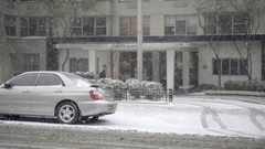 Taxi cab with Wicked ad driving past residential building snowing winter day NYC Stock Footage