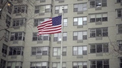 American flag waving in front of city building snowing in winter NYC Stock Footage