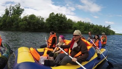 Summer rafting: group of tourists and travelers floating on river on raft Stock Footage