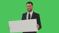 Medium Shot of a Smiling Businessman Holding Poster/Placard. Shot on a Green  Stock Footage