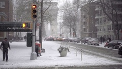 Snowing lower 5th Ave man crossing street snow Washington Square Park arch NYC Stock Footage
