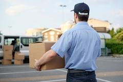 Portrait of confidence express courier next to his delivery van Stock Photos