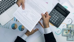 Man hands sign document, transfers hundred dollar bills to another mans hand Stock Footage
