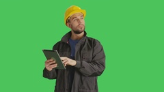 Mid Shot of a Handsome Worker Wearing Yellow Hard Hat Using Tablet Computer  Stock Footage