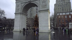 People walking in rain with umbrellas in Washington Square Park arch winter NYC Stock Footage