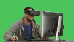 Mid Closeup Shot of a IT Man Wearing VR Headset Sitting at His Desktop Stock Footage