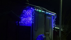 Christmas house lit garlands, winter snow-covered street, brick house lit with Stock Footage