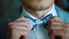 Wearing bow tie close up. Male hands check correct and adjust casual bow tie Stock Footage