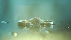 3 golden rings wedding and engagement lightened up from top extreme close up Stock Footage