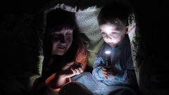 Happy mom and child play with the tablet under the covers Stock Footage